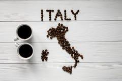 Kaart van Italië van geroosterde koffiebonen wordt gemaakt die op witte houten geweven achtergrond met twee koppen van koffie leg Royalty-vrije Stock Afbeelding