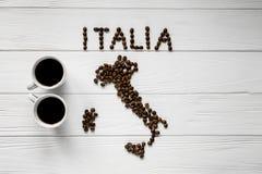 Kaart van Italië van geroosterde koffiebonen wordt gemaakt die op witte houten geweven achtergrond met twee koppen van koffie leg Stock Foto's