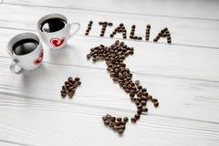 Kaart van Italië van geroosterde koffiebonen wordt gemaakt die op witte houten geweven achtergrond met twee koppen van koffie leg Royalty-vrije Stock Foto