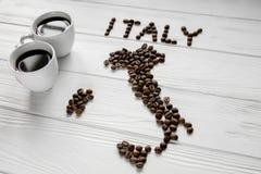 Kaart van Italië van geroosterde koffiebonen wordt gemaakt die op witte houten geweven achtergrond met twee koppen van koffie leg Royalty-vrije Stock Fotografie
