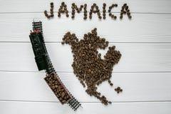 Kaart van Jamaïca van geroosterde koffiebonen wordt gemaakt die op witte houten geweven achtergrond met stuk speelgoed trein legg Royalty-vrije Stock Foto