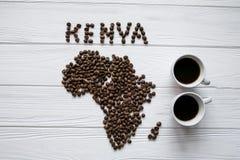 Kaart van Kenia van geroosterde koffiebonen wordt gemaakt die op witte houten geweven achtergrond met twee koppen van koffie legg Royalty-vrije Stock Afbeeldingen