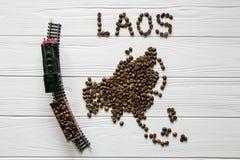 Kaart van Laos van geroosterde koffiebonen wordt gemaakt die op witte houten geweven achtergrond met stuk speelgoed trein leggen  Stock Afbeeldingen