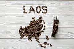 Kaart van Laos van geroosterde koffiebonen wordt gemaakt die op witte houten geweven achtergrond met stuk speelgoed trein leggen  Royalty-vrije Stock Foto