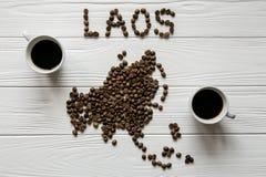 Kaart van Laos van geroosterde koffiebonen wordt gemaakt die op witte houten geweven achtergrond met twee koppen van koffie legge Stock Fotografie