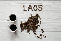 Kaart van Laos van geroosterde koffiebonen wordt gemaakt die op witte houten geweven achtergrond met twee koppen van koffie legge Royalty-vrije Stock Fotografie