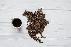 Kaart van Noord-Amerika van geroosterde koffiebonen wordt gemaakt die op witte houten geweven achtergrond met kop van koffie legg Stock Foto's