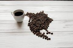 Kaart van Noord-Amerika van geroosterde koffiebonen wordt gemaakt die op witte houten geweven achtergrond met kop van koffie legg Stock Afbeelding