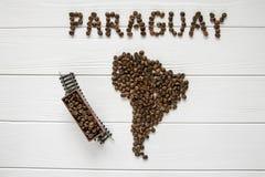 Kaart van Paraguay van geroosterde koffiebonen wordt gemaakt die op witte houten geweven achtergrond met stuk speelgoed trein leg Royalty-vrije Stock Foto's