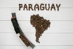Kaart van Paraguay van geroosterde koffiebonen wordt gemaakt die op witte houten geweven achtergrond met stuk speelgoed trein leg Stock Fotografie