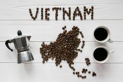 Kaart van Vietnam van geroosterde koffiebonen wordt gemaakt die op witte houten geweven achtergrond met koppen van koffie en koff Royalty-vrije Stock Afbeeldingen