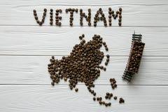Kaart van Vietnam van geroosterde koffiebonen wordt gemaakt die op witte houten geweven achtergrond met stuk speelgoed trein legg Stock Fotografie