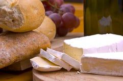 Kaas, brood, druiven en wijn op houten lijst stock afbeeldingen