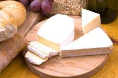 Kaas, brood, druiven en wijn op houten lijst stock foto's