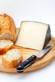 Kaas, brood en mes op houten plaat Royalty-vrije Stock Afbeeldingen