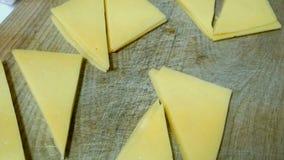Kaas, in driehoekige plakken wordt de gesneden, ligt op een houten keukenraad die stock video
