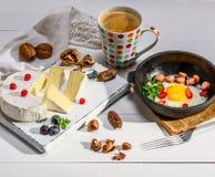 Kaas en een ronde zwarte gietijzerpan met een gebraden kuiken Stock Afbeeldingen