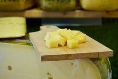 Kaas scherpe raad met Edammer kaaskubussen bovenop een blok van het kaaswiel royalty-vrije stock afbeeldingen