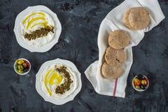 Kaas van het Middenoosten van de Labneh labaneh de zachte witte geitenmelk met olijfolie, olijven, za 'atar, citroen, met pitabro stock foto