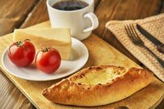 Kaaspastei met tomaten en kop van het stomen van thee of koffie op houten lijst Stock Afbeelding