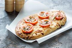 Kaaspizza met tomaten, kruiden en kruiden op een concrete backg Stock Afbeeldingen