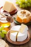 Kaasplaat met camembert, cheddar, druiven en honing stock foto's