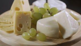 Kaasplaat met druiven, honing en noten die op grijze achtergrond roteren stock videobeelden