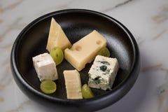 Kaasplaat met selectie Edamer, Parmezaanse kaas, geit, blauw en roomkaas, edele en druiven op zwarte schotel en marmeren achtergr royalty-vrije stock afbeeldingen