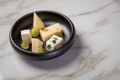 Kaasplaat met selectie Edamer, Parmezaanse kaas, geit, blauw en roomkaas, edele en druiven op zwarte schotel en marmeren achtergr stock afbeelding