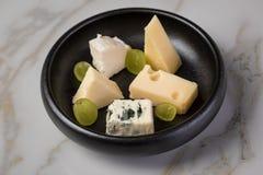 Kaasplaat met selectie Edamer, Parmezaanse kaas, geit, blauw en roomkaas, edele en druiven op zwarte schotel en marmeren achtergr royalty-vrije stock afbeelding