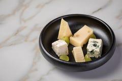 Kaasplaat met selectie Edamer, Parmezaanse kaas, geit, blauw en roomkaas, edele en druiven op zwarte schotel en marmeren achtergr stock fotografie