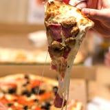 Kaasrek van een stuk van pizza met paddestoelen in de hand van een tiener Een vierkant beeld stock afbeelding