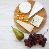Kaasschotel met vruchten op een witte houten achtergrond Voedsel voor wijn, hoogste mening Vlak leg hierboven, van Close-up royalty-vrije stock afbeeldingen