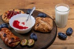 Kaastaart met jam, eigengemaakte yoghurt en een glas melk en een paar slokjes stock afbeelding