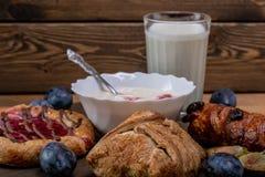 Kaastaart met jam, eigengemaakte yoghurt en een glas melk en een paar slokjes stock afbeeldingen