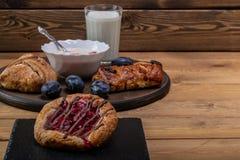 Kaastaart met jam, eigengemaakte yoghurt en een glas melk en een paar slokjes stock fotografie
