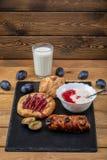 Kaastaart met jam, eigengemaakte yoghurt en een glas melk en een paar slokjes royalty-vrije stock afbeelding