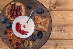 Kaastaart met jam, eigengemaakte yoghurt en een glas melk en een paar slokjes royalty-vrije stock fotografie