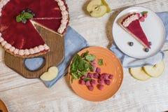 Kaastaart met jam op een houten die lijst, met frambozen, plakken van appelen en munt wordt verfraaid Royalty-vrije Stock Fotografie