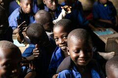 Kabala, Sierra Leone - June 3, 2019: African children at school in a remote village. Boys with happy and smiling faces learning