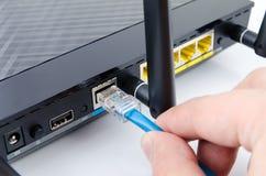 Kabel, das an modernen drahtlosen Wi-Firouter anschließt Lizenzfreies Stockfoto