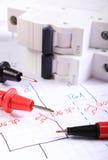 Kabel des Vielfachmessgerätstiftes und der elektrischen Sicherung auf elektrischer Zeichnung Stockfotos