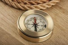 Kabel en kompas op houten stock afbeelding