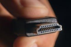 Kabel för handinnehavsvart HDMI Mannens hand rymmer ett HDMI-kontaktdon Kabel för Closeup HDMI Royaltyfri Fotografi