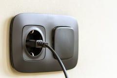 Kabel för kabel för svart makt pluggade in i europeiskt vägguttag på whit Arkivbild