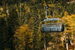 Kabelbaan hoog in de bergen boven het de herfstbos stock afbeeldingen