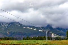 Kabelbaan op bergen en gele gebieden, de herfstlandschap, bewolkte hemel royalty-vrije stock afbeelding