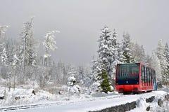 Kabelbaancabine op sporen in bergen in mist Stock Foto's