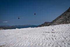Kabelbahn bei dem Transport über einer schneebedeckten Skisteigung lizenzfreie stockbilder