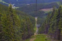 Kabelbahn am Berg-Schnee, der durch den Kiefernwald überschreitet Lizenzfreie Stockfotografie